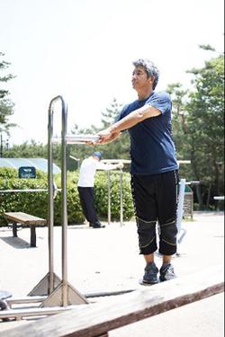 중년 남성이 공원에서 운동하고 있다.